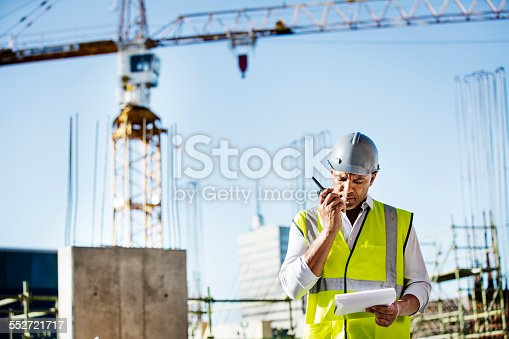 istock Architect using walkie-talkie at construction site 552721717