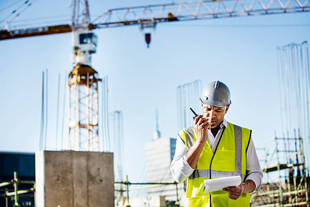 Architect using walkie-talkie at construction site stock photo
