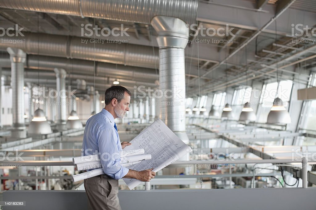 Architect viewing blueprints stock photo