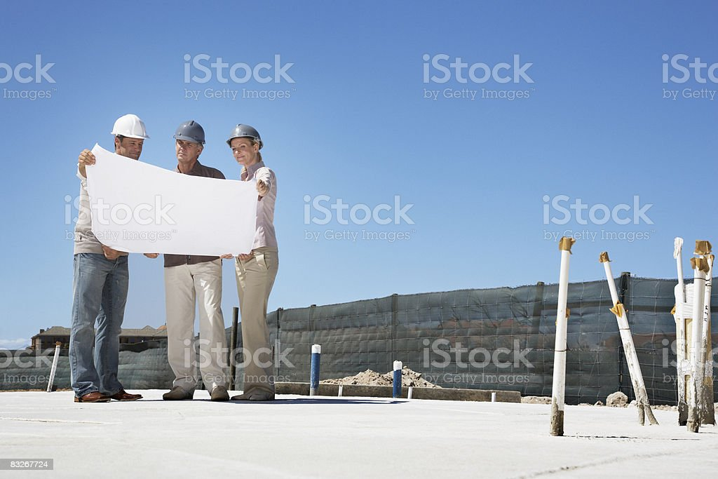 Architect viewing blueprints with home owners stock photo