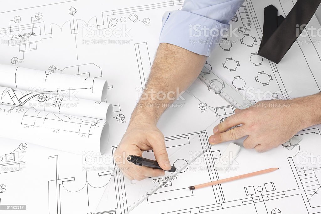 Businessman is drawing on blue prints.