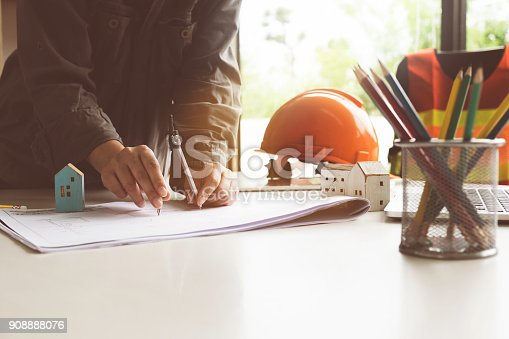 istock Architect woman working with compasses and blueprints for architectural plan,engineer sketching a construction project concept. 908888076
