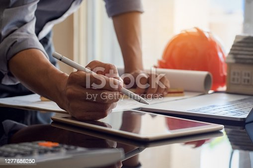 Architect man or male engineer work on digital tablet with blue print and laptop computer on the desk at office.
