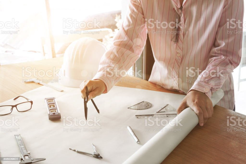 architect working and sketching architectural drawing plan on table in office – Foto