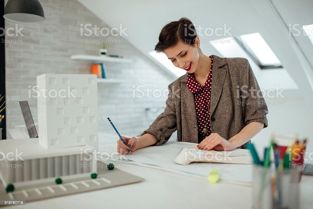 Female architect working in her new modern office. Standing and...