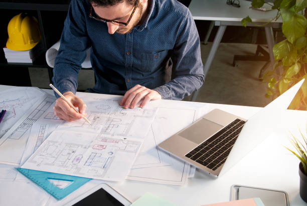 Architect working in office with house project on desk stock photo