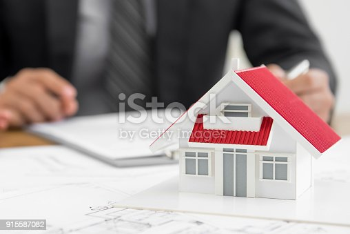 istock Architect working on a  house model 915587082