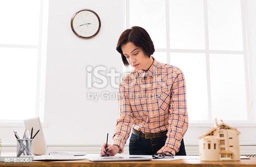 832105172 istock photo Architect working on blueprint in office 857829064