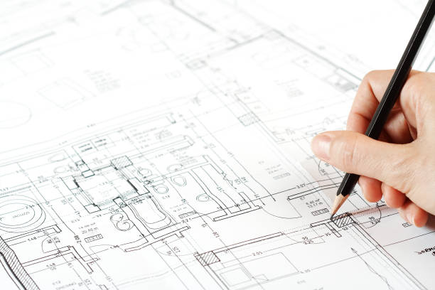 Architect working on blueprint projects stock photo