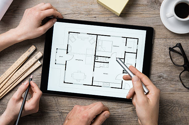 Architect working on digital tablet Team of architects working on the house project on a wooden table. Top view of hands pointing architectural project on digital tablet. Interior designer hand working with digital tablet. interior designer stock pictures, royalty-free photos & images