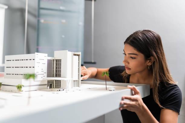 architekt arbeitet über modell im büro - architekturberuf stock-fotos und bilder
