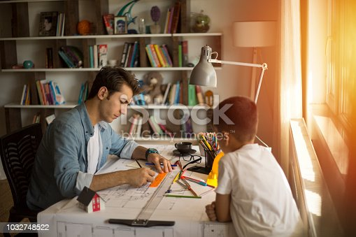 istock Architect working with blueprints in the home office. 1032748522