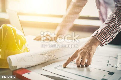 istock Architect working with blueprints in the office. 832104872