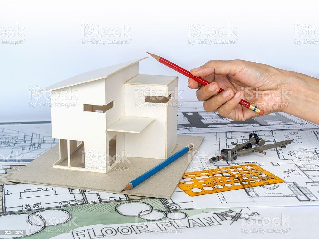 Architect working with house model blueprints housing development architect working with house model blueprints housing development business royalty free stock photo malvernweather Images