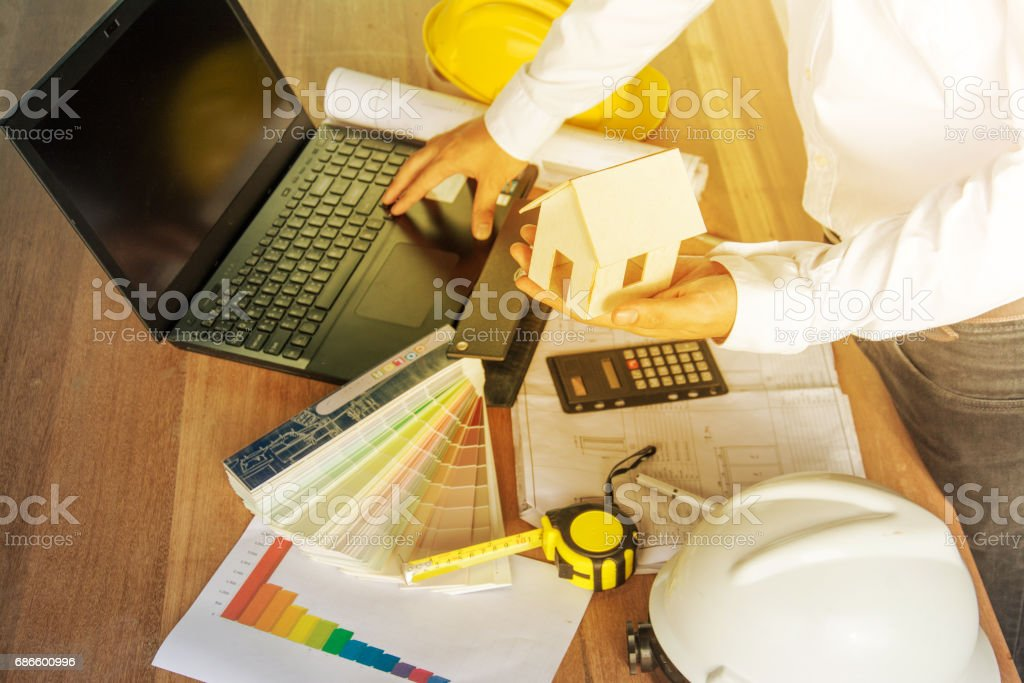 architect  working with laptop ,model and blueprints on wood table,  vintage stlye color royalty-free stock photo