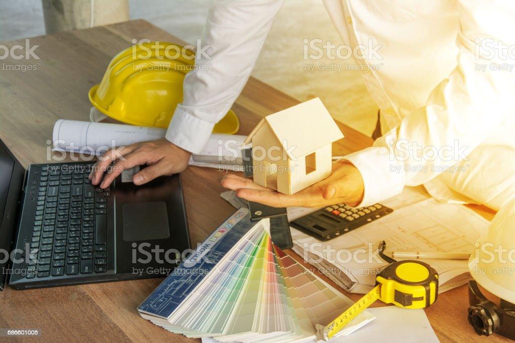 l'architecte de travail avec ordinateur portable, modèle et plans sur table en bois, style vintage couleur photo libre de droits