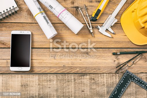istock Architect workplace. Smartphone with black blank screen, project construction blueprints and engineering tools on wooden desk, copy space, top view 1031809498