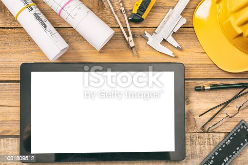 994878714 istock photo Architect workplace. Tablet with white blank screen, project construction blueprints and engineering tools on wooden desk, copy space, top view 1031809512