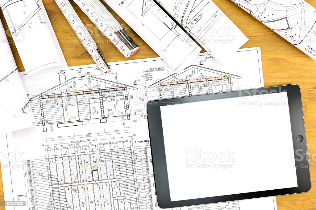 architect workplace with tablet blueprint and rolls of plans stock photo