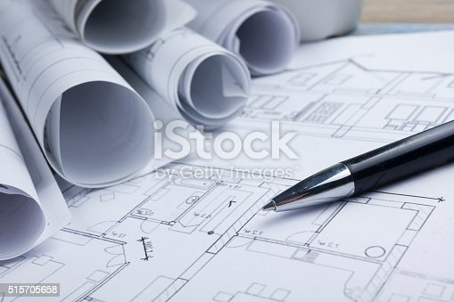 515801338 istock photo Architect worplace top view. Architectural project, blueprints, blueprint rolls and 515705658