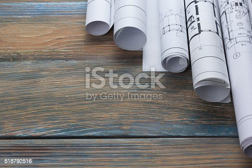 515801338 istock photo Architect worplace top view. Architectural project, blueprints, blueprint rolls on 515792516