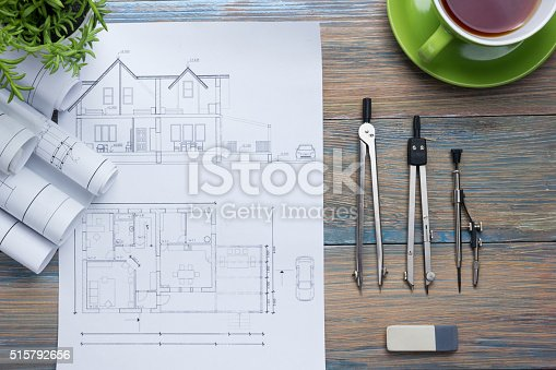 515801338 istock photo Architect worplace top view. Architectural project, blueprints, blueprint rolls and 515792656