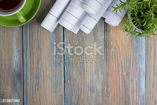515801338 istock photo Architect worplace top view. Architectural project, blueprints, blueprint rolls and 515801580