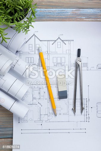 515801338 istock photo Architect worplace top view. Architectural project, blueprints, blueprint rolls and 515925274