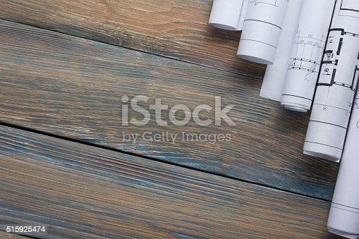 515801338 istock photo Architect worplace top view. Architectural project, blueprints, blueprint rolls on 515925474