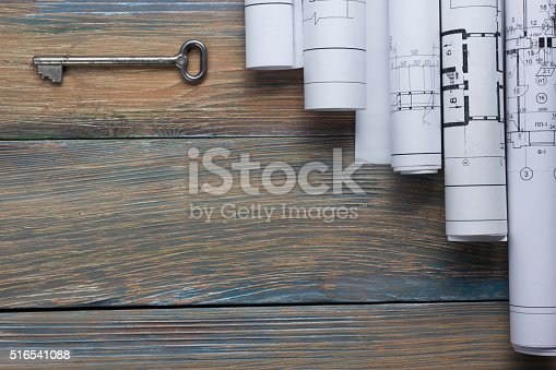 515801338 istock photo Architect worplace top view. Architectural project, blueprints, blueprint rolls and 516541088