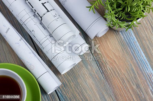 515801338 istock photo Architect worplace top view. Architectural project, blueprints, blueprint rolls and 516544356
