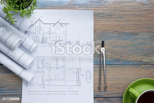515801338 istock photo Architect worplace top view. Architectural project, blueprints, blueprint rolls and 517236898