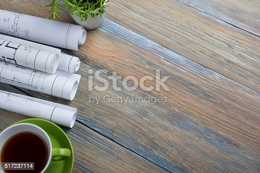 515801338 istock photo Architect worplace top view. Architectural project, blueprints, blueprint rolls and 517237114
