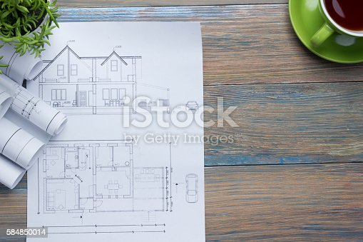 515801338 istock photo Architect worplace top view. Architectural project, blueprints, blueprint rolls and 584850014