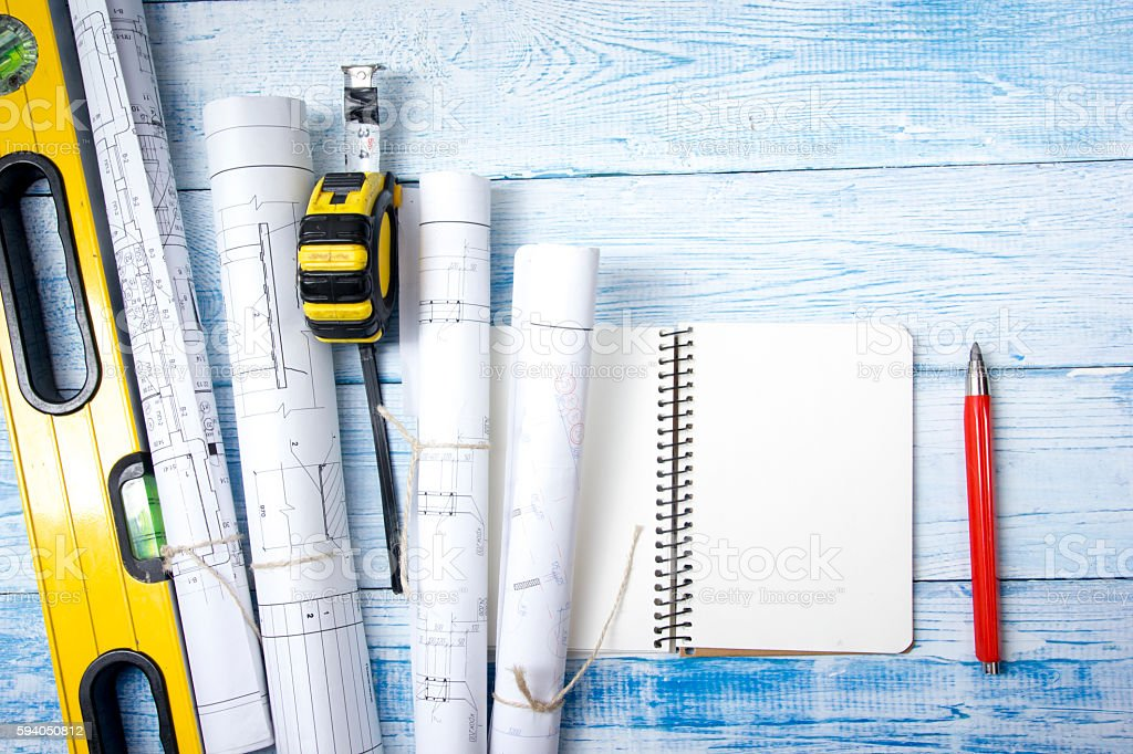 Architect worplace top view. Architectural project, blueprints, blueprint rolls on stock photo