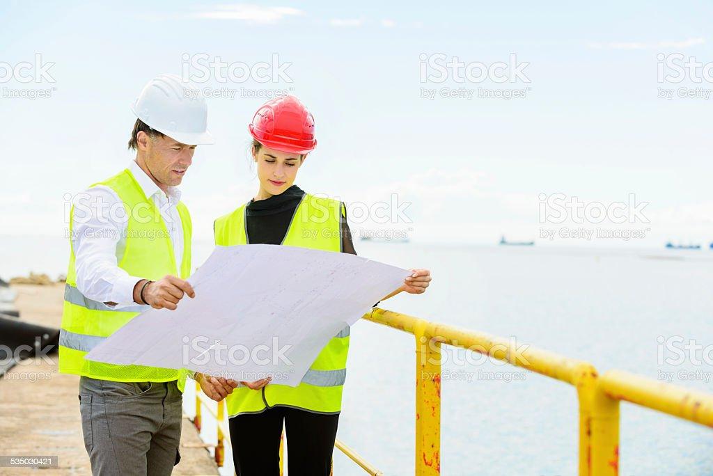 Architects analyzing blueprint together on commercial dock by sea architects analyzing blueprint together on commercial dock by sea royalty free stock photo malvernweather Images