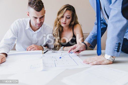 938640610 istock photo Architects and clients looking at blueprints 1180087224