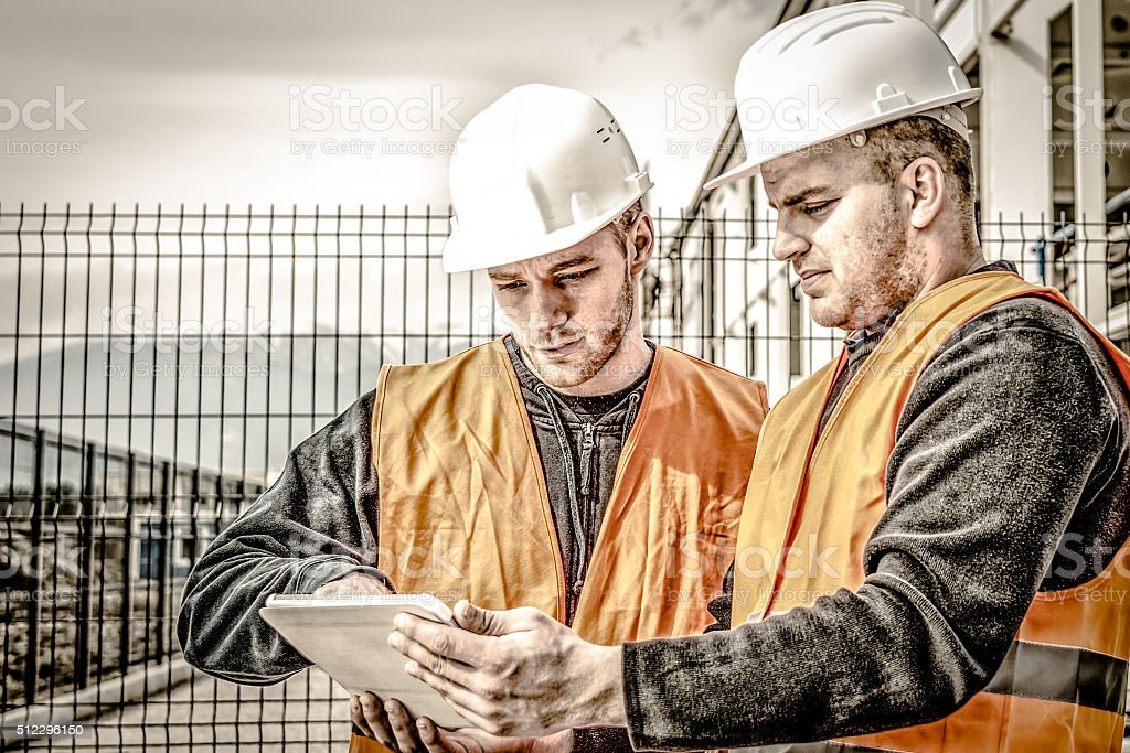 Architects at a building site with digital tablet stock photo