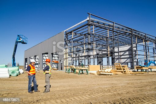 A royalty free image from the construction industry of two architects at a steel frame building site.