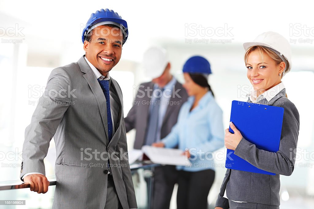 Architects at their workplace. In the foreground two co-workers royalty-free stock photo