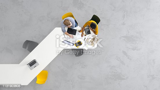 Overhead view of two architects working on a project in the office