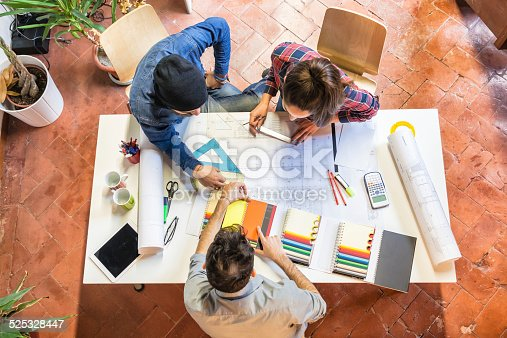 istock Architects at work studying a blueprint 525328447