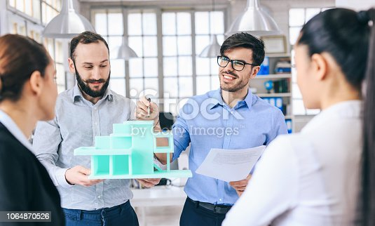 532257236istockphoto Architects discussing new project 1064870526