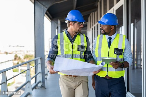 Metalworker and engineer meeting at construction site. Multiethnic architects in construction site with safety equipment walking and discussing. Architect and engineer working together while visiting a new building.