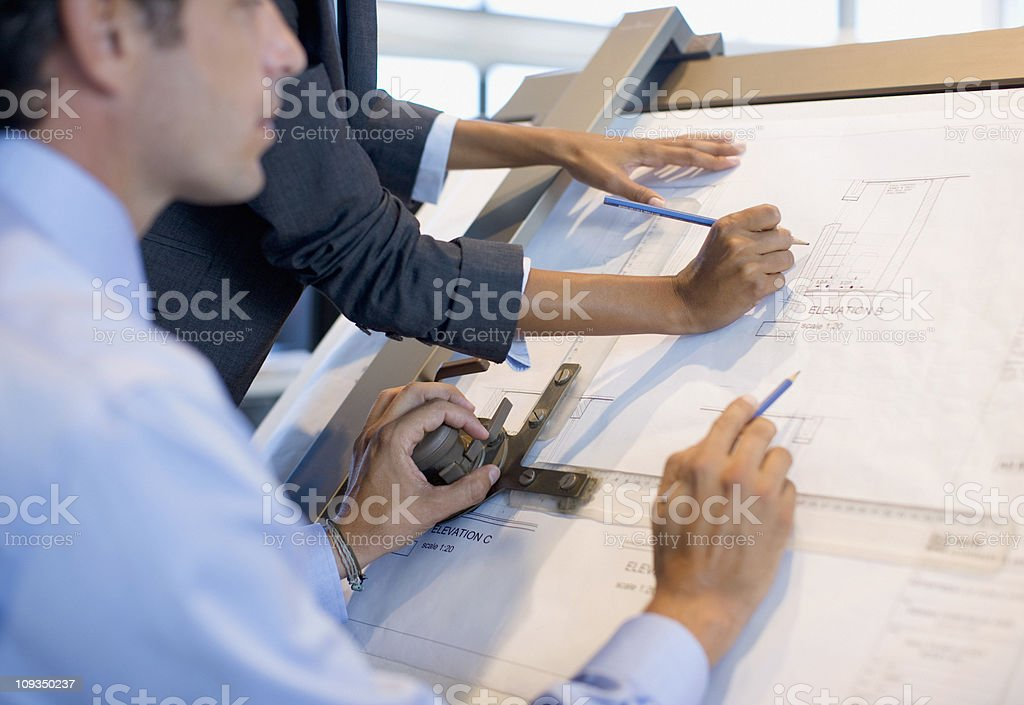 Architects drawing blueprints together in office stock photo