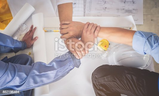 912867216istockphoto Architects, engineers and businessmen are joining hands for unity. To work together as a team to work successfully. 852196454