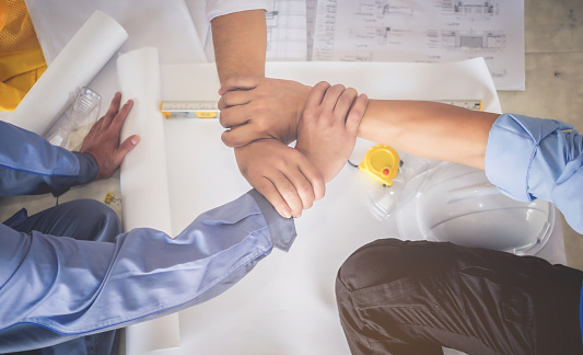 912867216 istock photo Architects, engineers and businessmen are joining hands for unity. To work together as a team to work successfully. 852196454