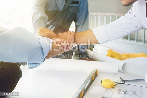 912867216istockphoto Architects, engineers and businessmen are joining hands for unity. To work together as a team to work successfully. 865996938
