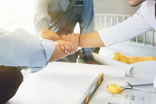 912867216 istock photo Architects, engineers and businessmen are joining hands for unity. To work together as a team to work successfully. 865996938