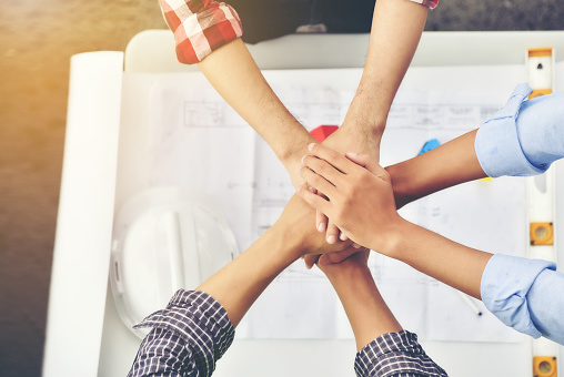 912867216 istock photo Architects, engineers and businessmen are joining hands for unity. To work together as a team to work successfully. 918813488